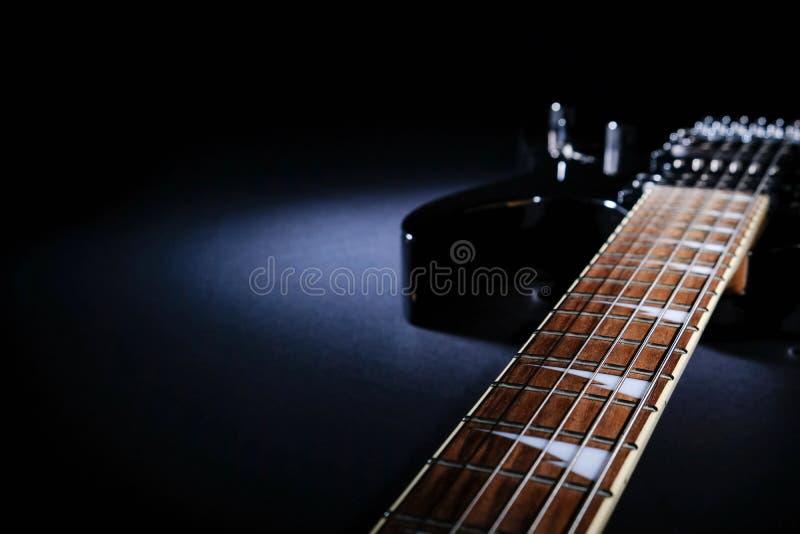 Modern svart elektrisk gitarr Närbild av fingerboarden under stråle av ljus Med avst?nd f?r text royaltyfri fotografi