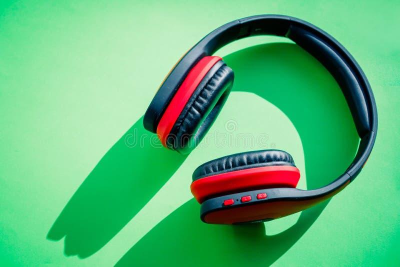 Modern svart och röd trådlös hörlurar på en grön bakgrund Begreppet av musik och mode Plan minsta stil royaltyfria bilder