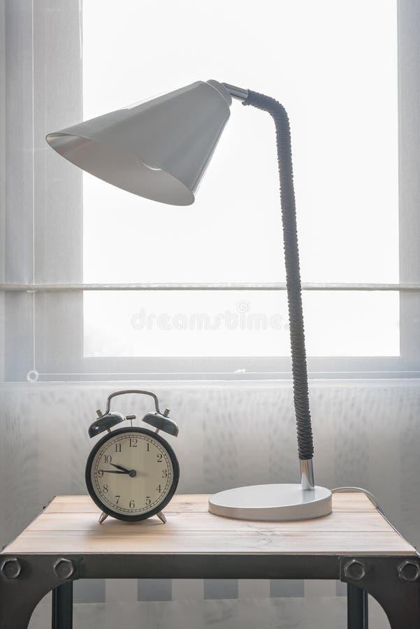 Modern svart ringklocka med den moderna vita lampan arkivfoto