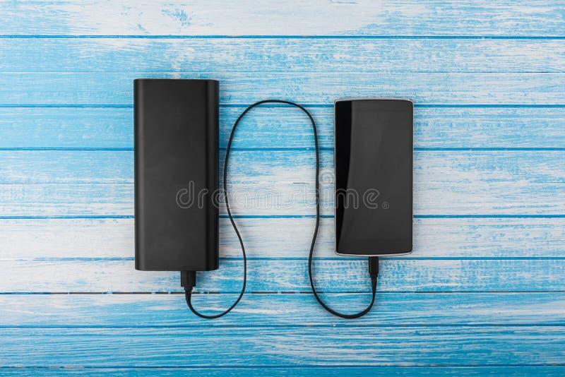Modern svartSmart telefon med det tömda batteriet förbindelse till stort E royaltyfria foton