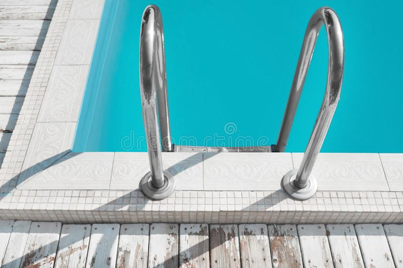 Modern swimming pool with ladder. At resort royalty free stock photography