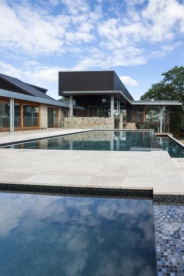 Modern swimming poolside with a luxury house or hotel stock photography