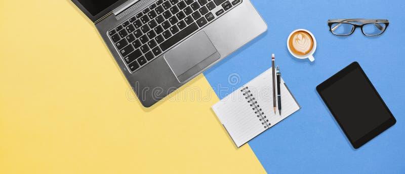 Modern tabell för färgkontorsskrivbord med bärbara datorn, anteckningsboken, minnestavlan och varmt kaffe med kopieringsutrymme arkivfoton