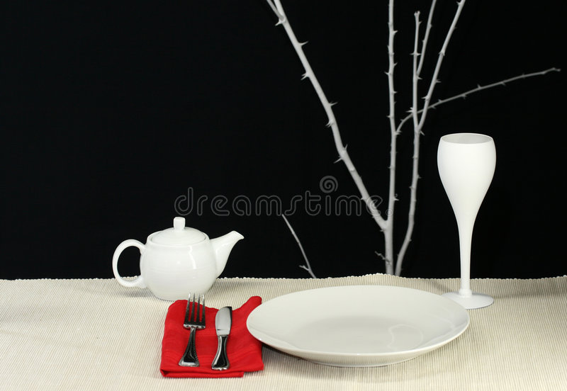 Modern Table. An elegant modern table set for dinner in black and white with red accent stock photos