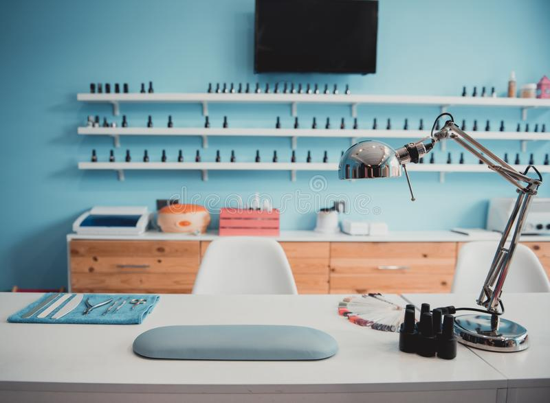 Manicure utensils and equipment locating on desk. Modern table with nails color palette and lamp situating in salon. Interior concept royalty free stock photo