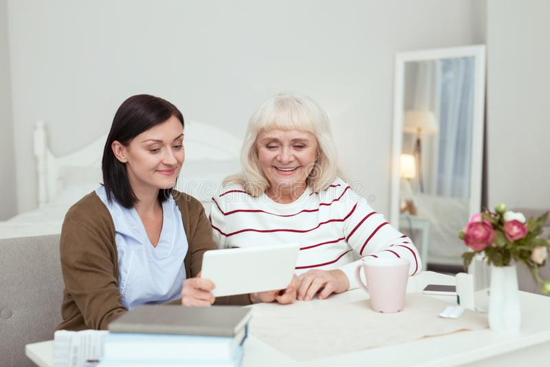 Happy elder woman and caregiver watching movie. Modern tablet. Gay elder women and caregiver using tablet while smiling stock images