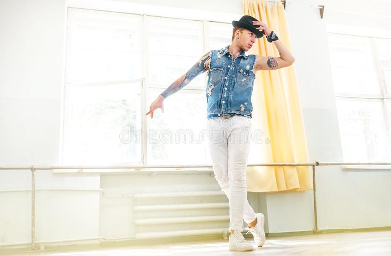 Modern tattooed art dancer teenager dressed in jeans vest, white pants and black hat dancing and mirror posing portrait royalty free stock images