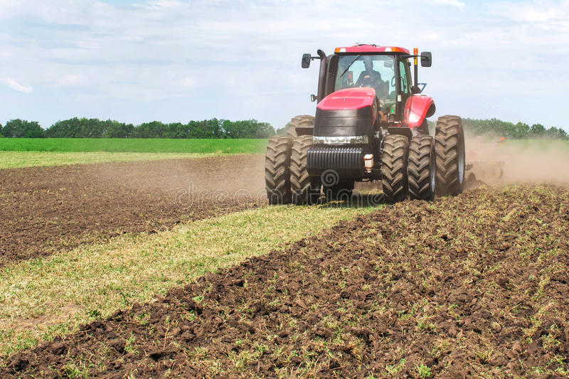 Modern tech red tractor plowing a green agricultural field in spring on the farm. Harvester sowing wheat. stock photography