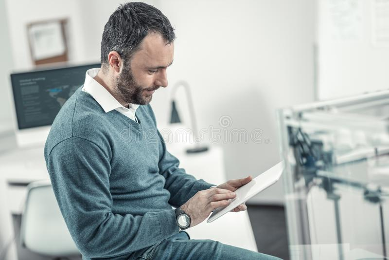 Smart nice adult man using modern device. Modern tech. Smart nice man using a modern device while working in the office stock photo