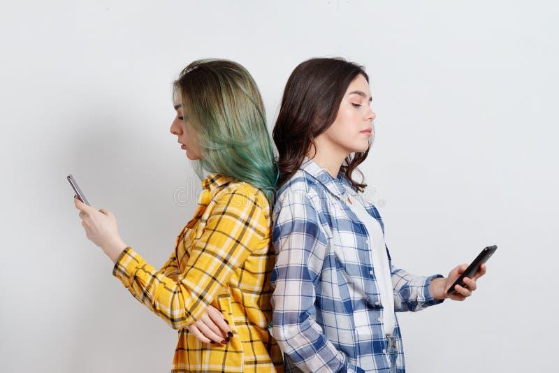Modern technologieën en Internet-verslavingsconcept Jonge vrouw twee die zich rijtjes, geabsorbeerd in elektronische gadgets, nie stock foto