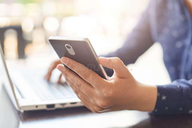 Modern technologie en levensstijlconcept Een close-up van vrouwen` s handen die smartphone houden en iets typen bij haar laptop E royalty-vrije stock afbeeldingen