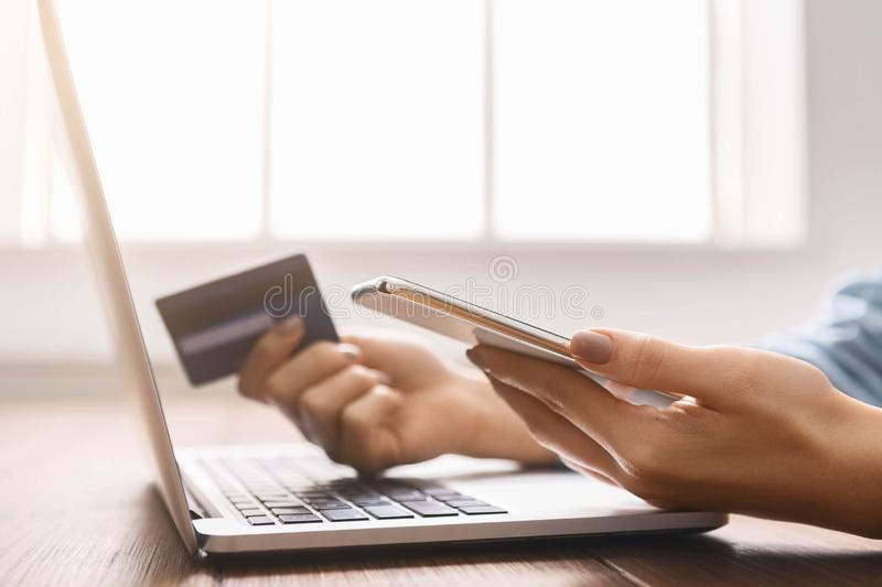 Young businesswoman booking tickets online using smartphone and credit card. stock photo