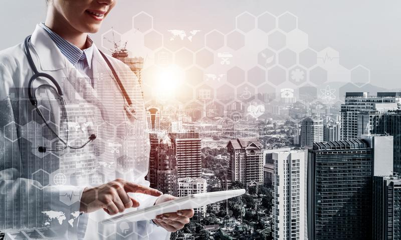 Modern technologies for medical industry. Double exposure of young woman doctor in white medical suit touching tablet with her finger and city view and medical stock illustration