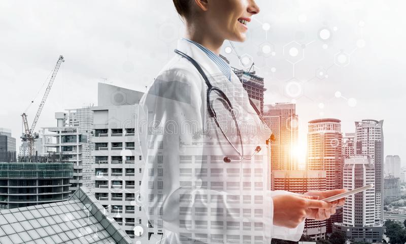 Modern technologies for medical industry. Side view of cheerful female doctor in sterile suit holding tablet in hands and smiling while standing against city vector illustration