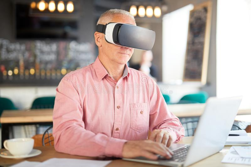 Modern technologies. Senior businessman using latest technological innovations while working by table in cafe royalty free stock photo