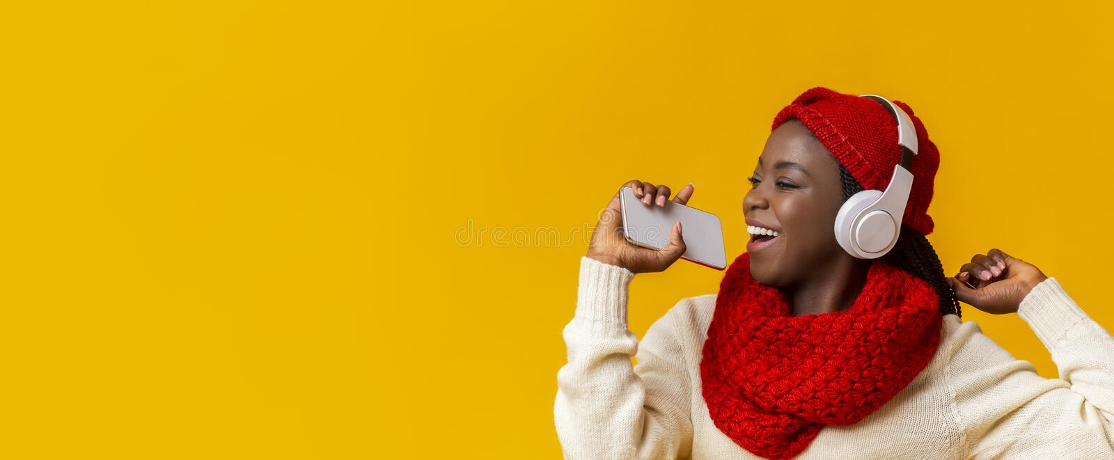 Carefree winter girl in wireless headset singing in phone stock images
