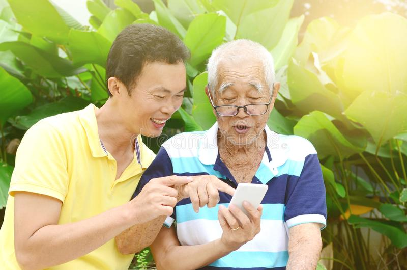 Asian family. Modern technology, age and people concept. Asian family using smart-phone. Family living lifestyle at garden royalty free stock photography