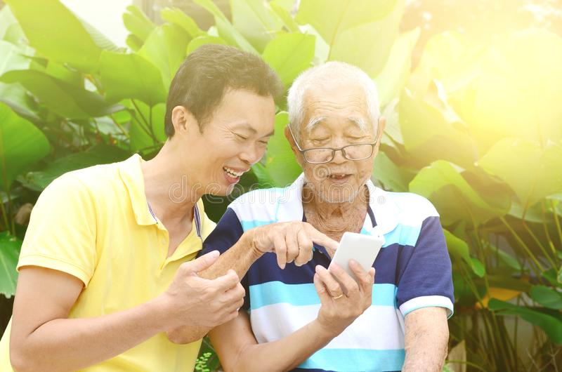 Asian family. Modern technology, age and people concept. Asian family using smart-phone. Family living lifestyle at garden stock image
