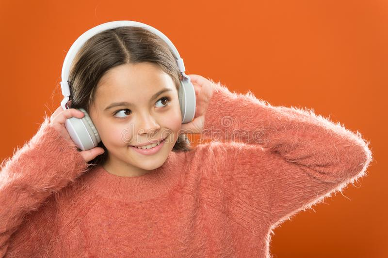 Modern technology is amazing. Small child wearing headphones with bluetooth technology. Little girl listening to music stock images