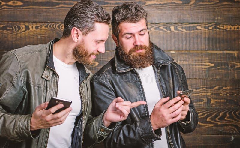 Modern technology. Men with smartphones surfing internet. Mobile internet. Business application. Men brutal bearded royalty free stock image