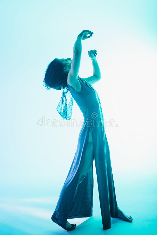 Modern teen contemporary dancer poses in front of the studio background. stock photos