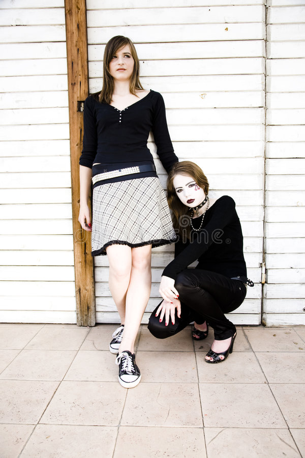 Modern Teenage Life. Two Girls Against Wooden Wall royalty free stock images