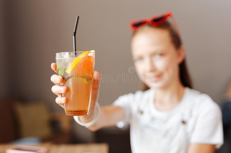 Modern teenager holding refreshing cocktail in her hands stock images