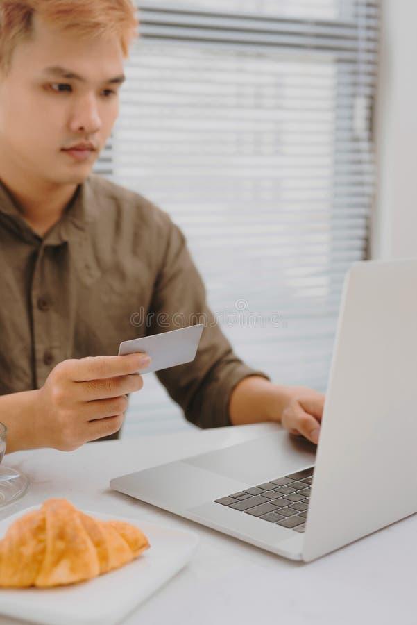 Modern teknologi, affär, karriär, e-kommers och online-handelbegrepp Den asiatiska affärsmaninnehavkreditkorten i en hade och royaltyfri bild