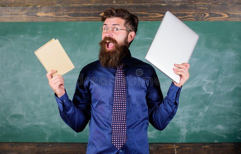 Modern teknologifördel Stag som är modernt med teknologi Lärare uppsökte hipsterhåll bok och bärbar dator lärare arkivfoto