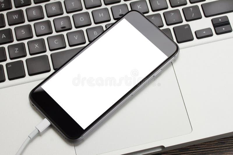 Modern telefon som lägger på bärbar datortangentbordet royaltyfri fotografi