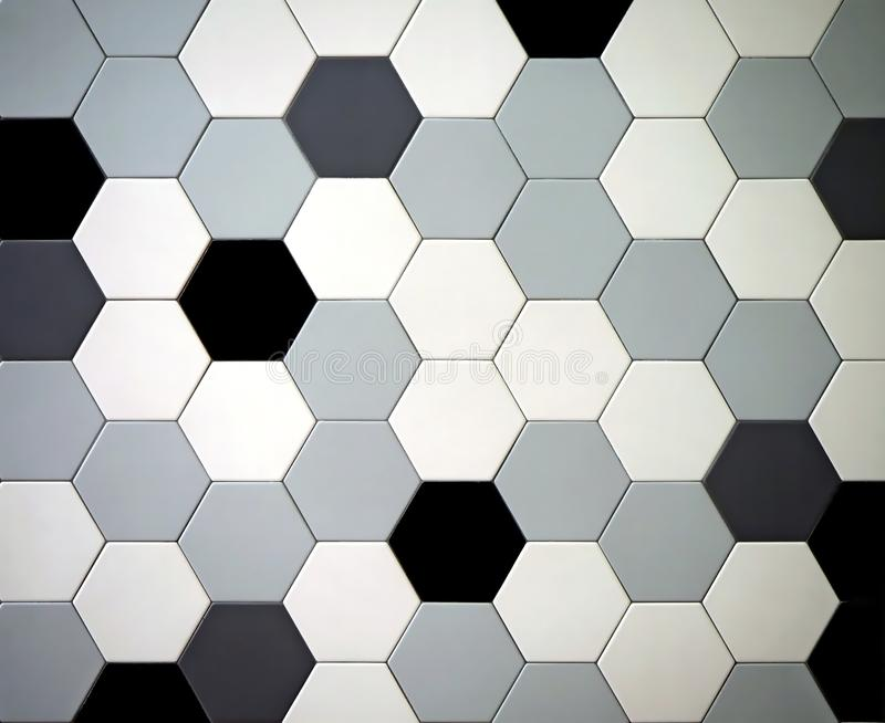 Modern tiled floor with hexagonal tiles. Colors are black,white, light and dark gray randomly arranged stock photography