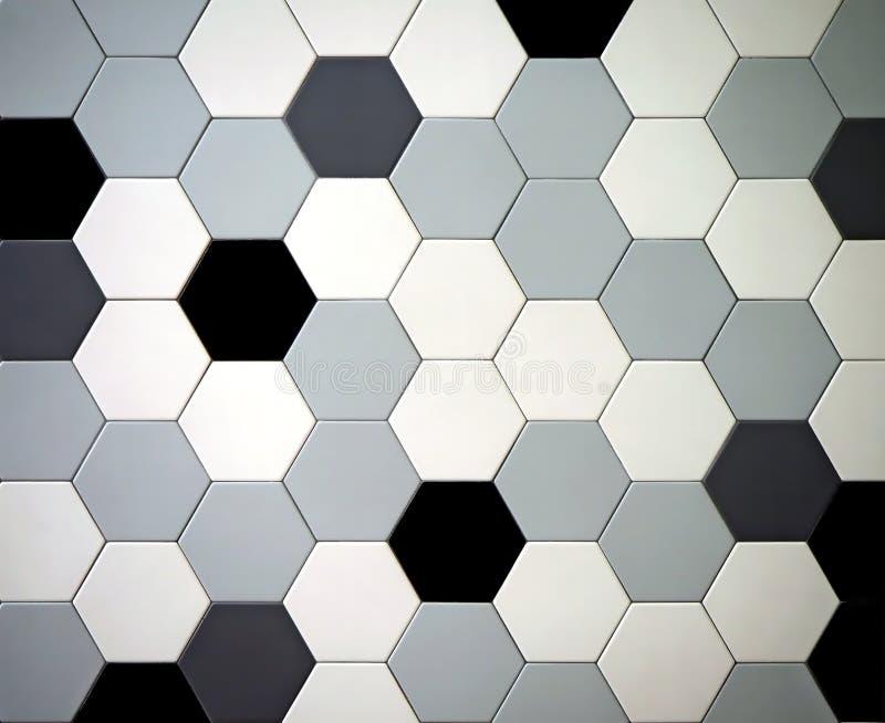 Modern tiled floor with hexagonal tiles. Colors are black,white, light and dark gray randomly arranged.  stock photography
