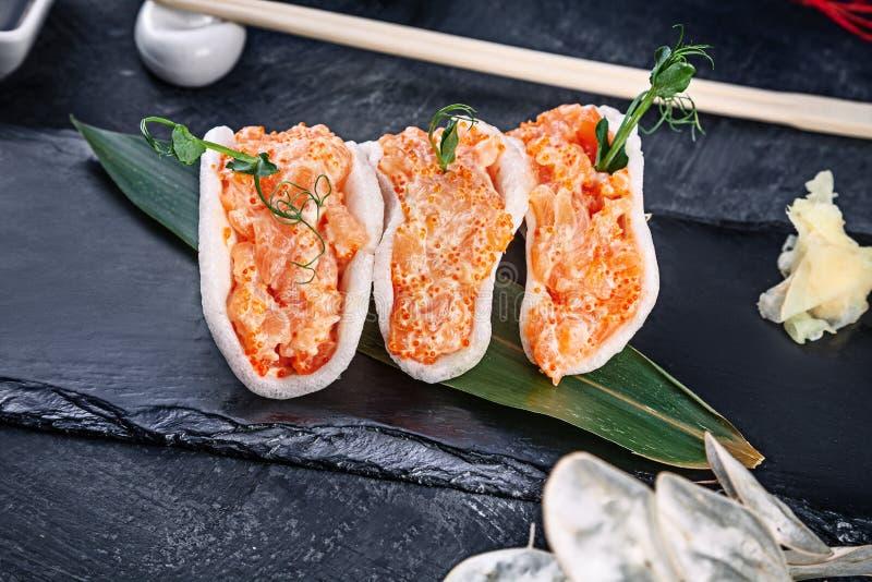 Modern tjänande som laxtandsten med avokadot i rischiper sund mat r? skaldjur den rå laxen med microgreen och den Tobiko kaviaren royaltyfria foton