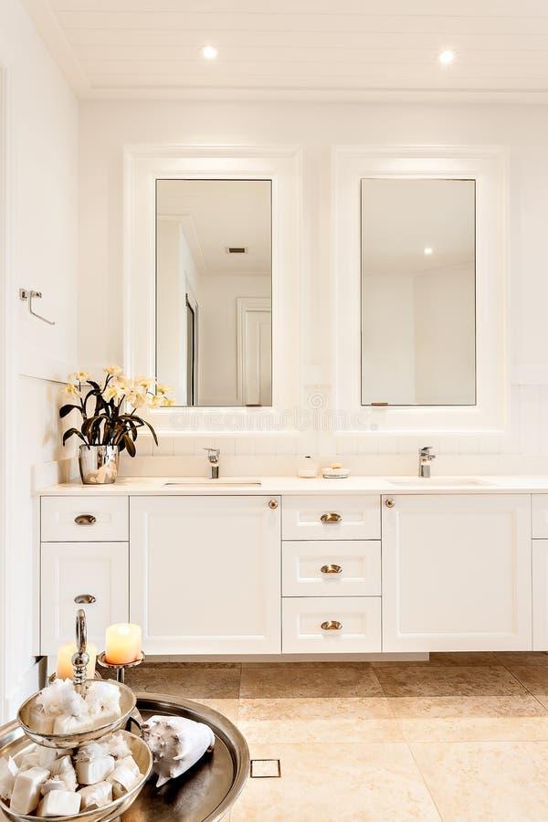 Modern toalett med två speglar i ett lyxigt hus arkivfoton