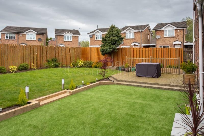 Modern trädgård med en ny planterad gräsmatta royaltyfri fotografi