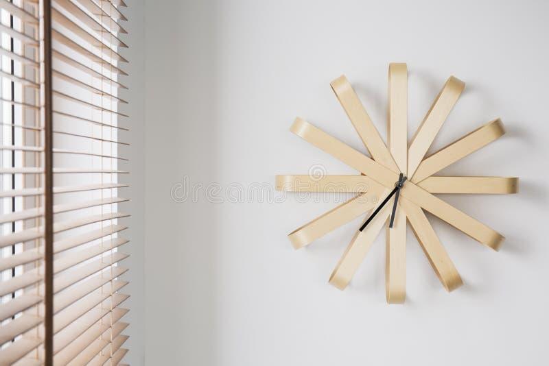 Modern träklocka på den vita väggen bredvid fönster med rullgardiner i enkel plan inre Verkligt foto royaltyfri foto