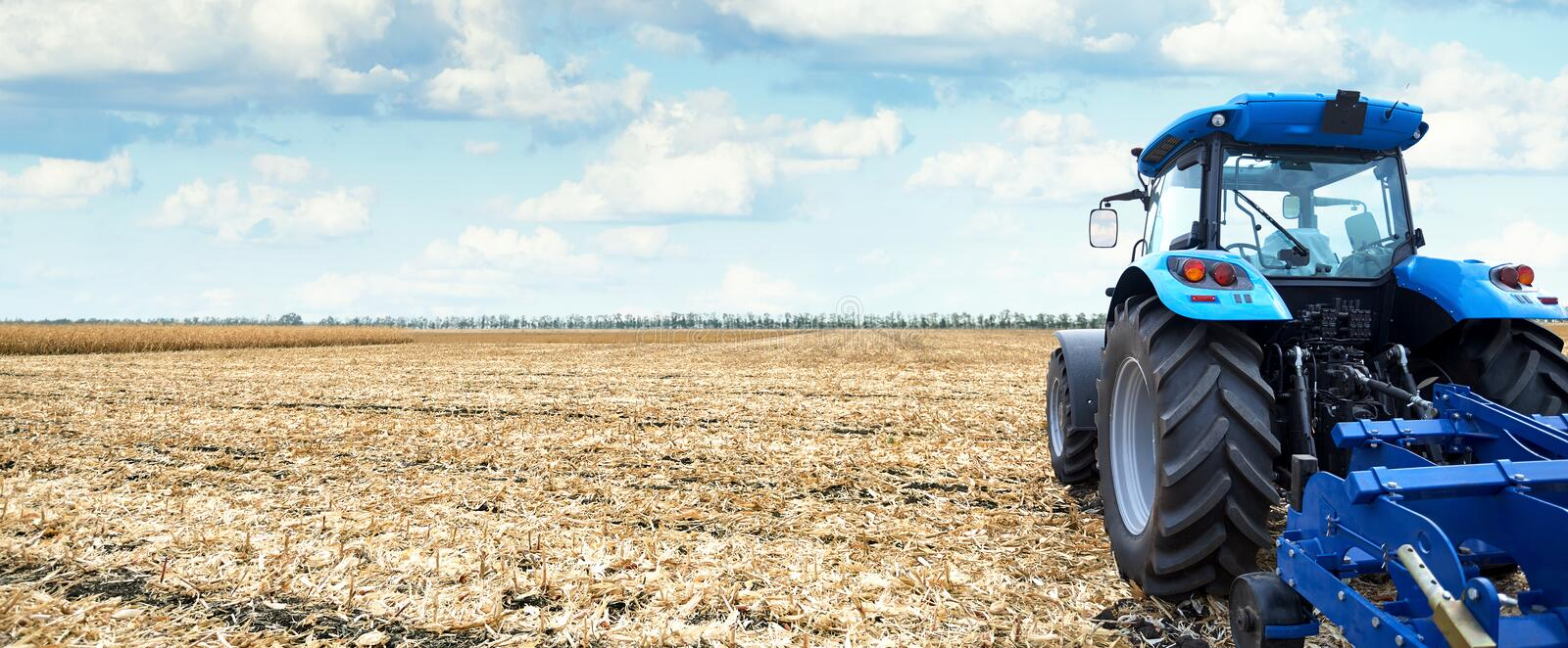 Modern tractor is working in the field. Tractor working on the farm, a modern agricultural transport, cultivation of fertile land, tractor on cloudy sky stock photography