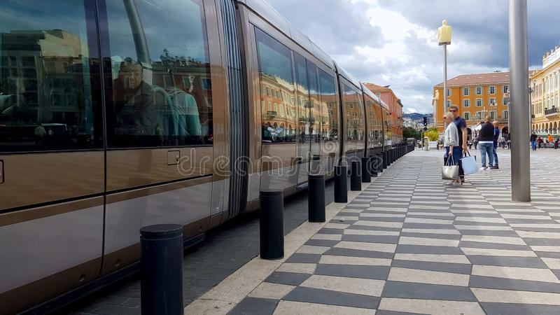 Modern train stops on Nice square, passengers waiting for next vehicle, Europe royalty free stock image