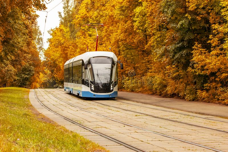 Modern tram on the background of autumn foliage. Rail ecological city transport on the background of the autumn landscape, stock images