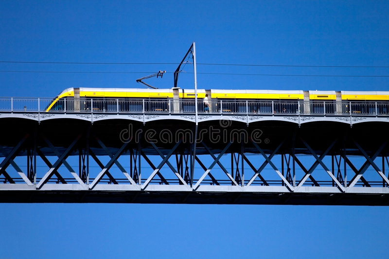 Modern tram on a steel bridge. Against a clear blue sky stock images