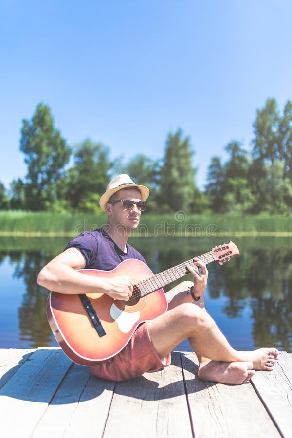 Modern trendig man som sitter på träpir och spelar den akustiska gitarren med den härliga sjön i bakgrunden Musik och fotografering för bildbyråer