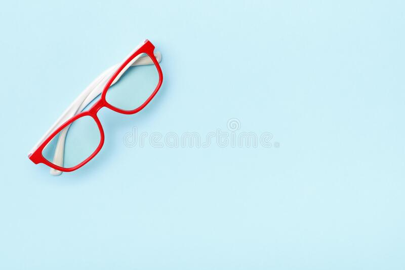 Modern trendy glasses in red frames on a blue background. Copy space stock images