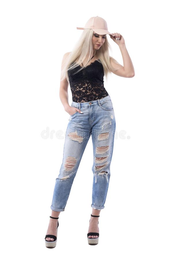 Modern trendy stylish look blonde girl posing with cap looking down holding visor. Full body isolated on white background royalty free stock photos