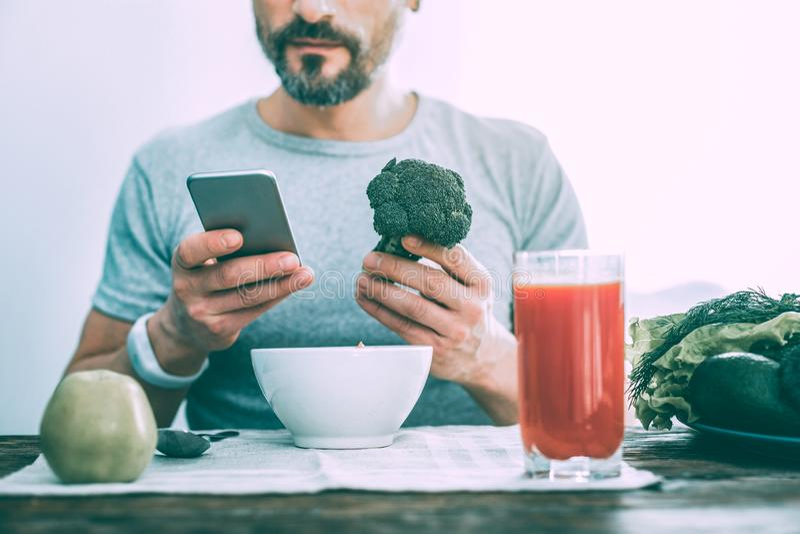 Modern trevlig man som rymmer broccoli i handen arkivfoton