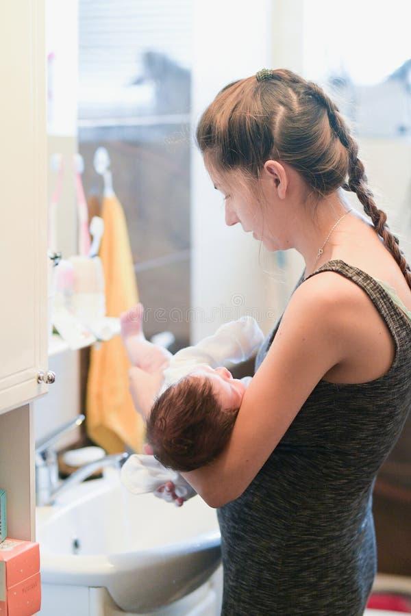 Modern tvättar barnet Den oigenkännliga mamman badar hennes son i vasken royaltyfri foto