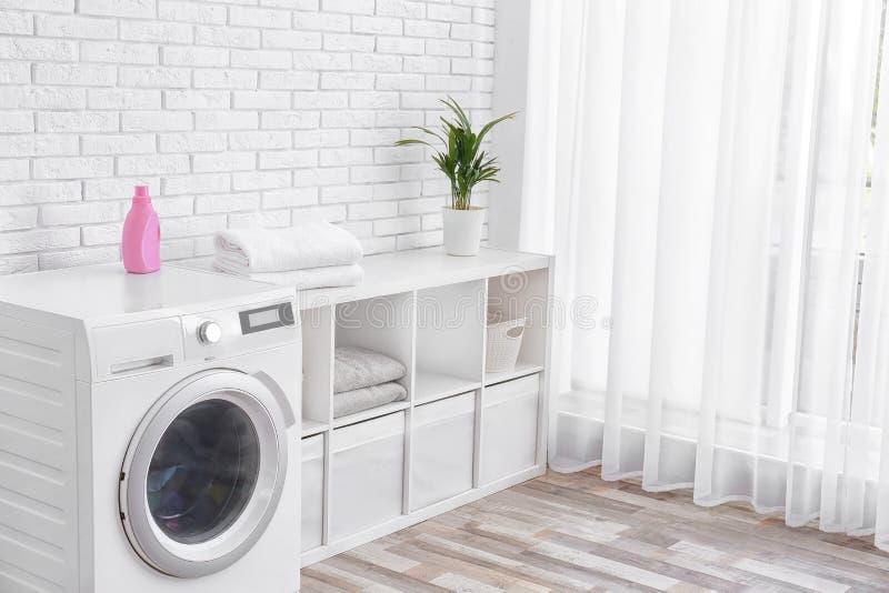 Modern tvättmaskin nära väggen i tvättstugainre, utrymme för text royaltyfria foton