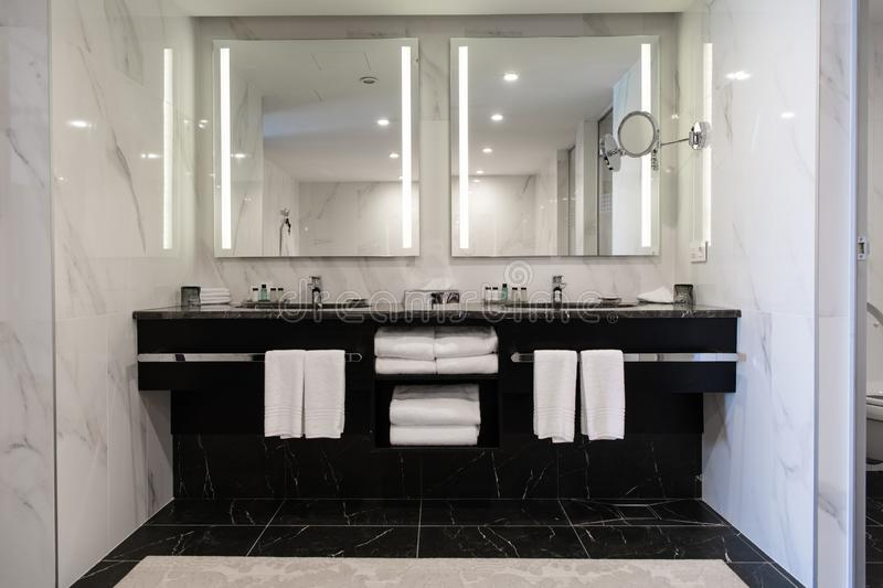 Modern twin bathroom with sinks, mirrors and towels.  royalty free stock photo