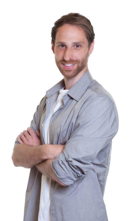 Modern tysk grabb med skägget och korsade armar i grå skjorta royaltyfria bilder