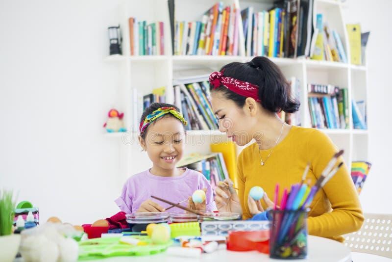 Modern undervisar hennes dotter att måla påskägg royaltyfri foto