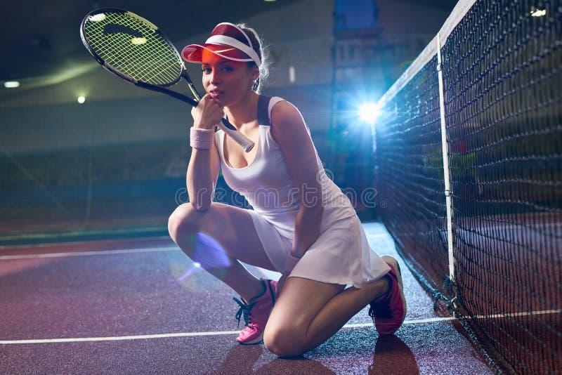 Modern ung kvinna som poserar på tennisbanan royaltyfri fotografi